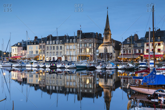 May 30, 2018: Sailing boats in front of illuminated waterfront houses and ancient church in the beautiful picturesque port of honfleur, dusk, blue hour, calvados, seine-maritime, basse-normandy