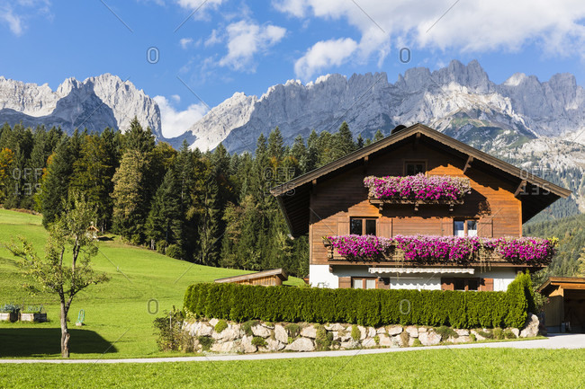 Typical house with geranium flower boxes in front of the mountain range 'wilder kaiser'