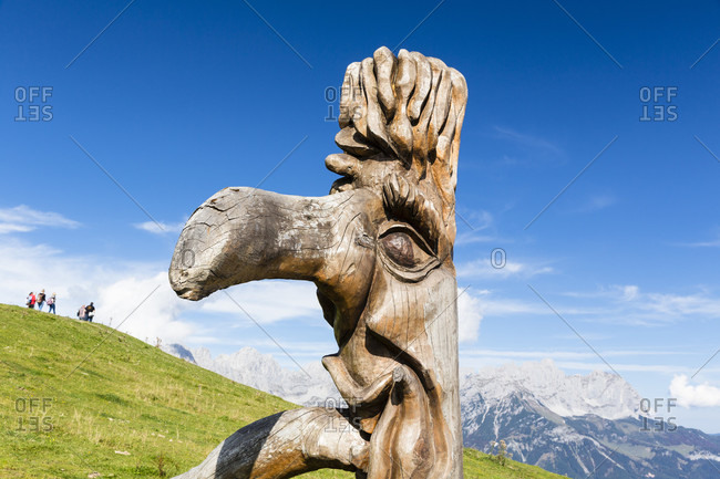 May 30, 2018: Carved wodden figure on mount hartkaiser (1.555 m) in front of mountain range 'wilder kaiser', autumn