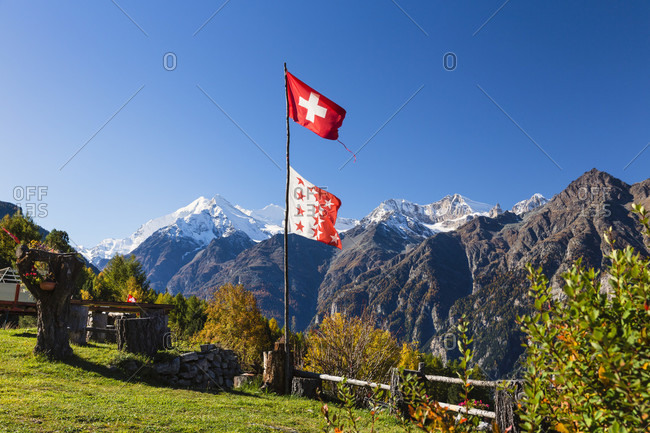 Swiss flagg in front of weisshorn mountain group, autumn