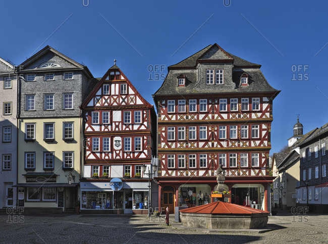 March 23, 2020: Europe, germany, hesse, lahn-dill-bergland nature park, city of herborn, market square, nassauer haus (markt 2), four-story half-timbered house with flat carvings, built in 1728, market fountain
