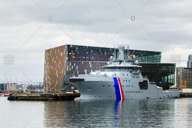 July 8, 2019: Reykjavik harbor with harpa opera house in the background, the famous concert hall and conference center of the danish company henning larsen architects with olafur eliasson