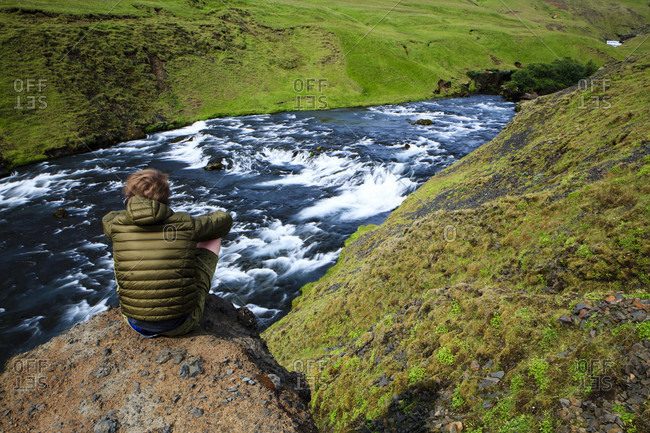 Iceland, man sitting on a river
