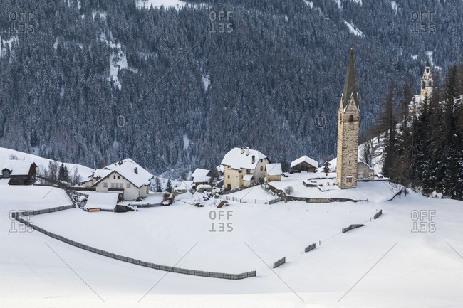Alpine village of tolpei with the st. barbara chapel in winter, la vallewengen, val badia, bolzano, dolomites, south tyrol, italy