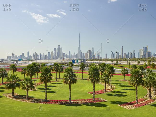 January 16, 2020: Skyline, green meadows, palm trees, flowers, dubai, united arab emirates