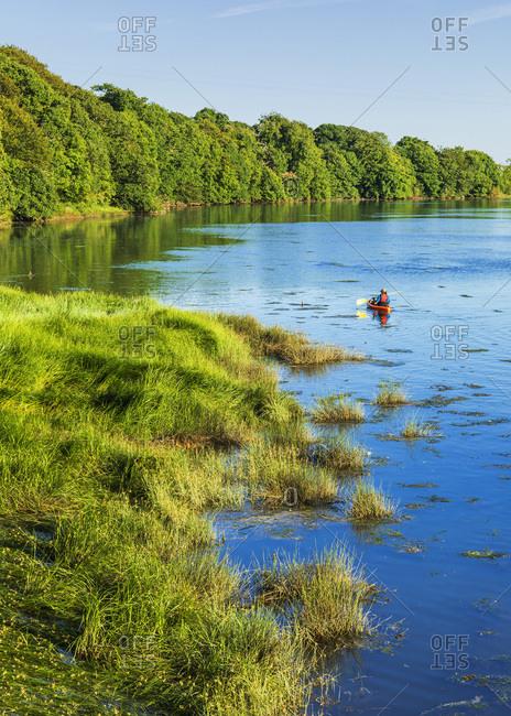 People kayaking on a tidal river near Tintern Abbey