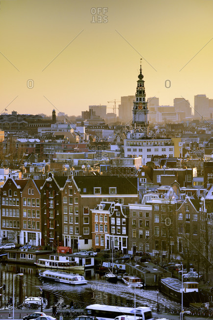 Netherlands - February 2, 2014: View over Amsterdam at sunset as seen from an elevated position with Montelbaan Tower among typical Dutch houses and canals.