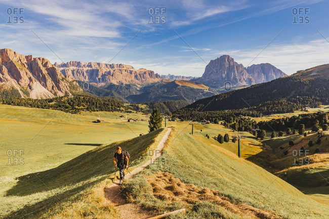 Italy - September 9, 2020: Woman hiking at Alpe di Seceda located on the sunny side of Val Gardena, with Sassolungo (Langkofel) in the background
