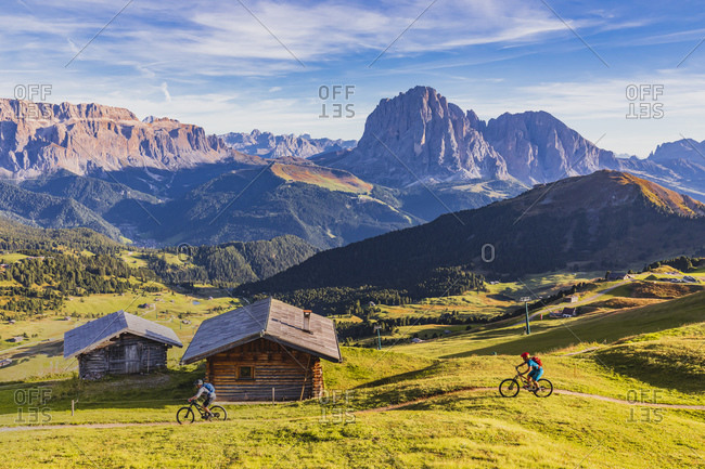 Cyclists riding mountain bikes at Alpe di Seceda located on the sunny side of Val Gardena, at the foot of the Parco Naturale Cisles-Odle, with Sassolungo (Langkofel) in the background