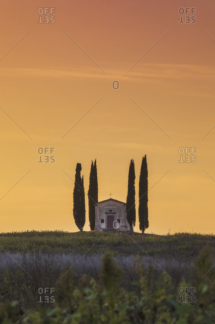 Italy - September 9, 2020: Little church with two cypresses on the top of a hill at sunset