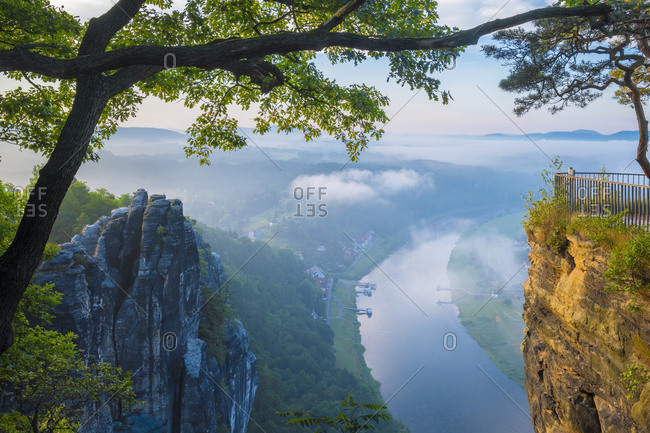Dawn on the Bastei rocks and the harbor of the village, along the Elba river, in background, view from Lohmen