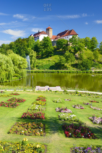 Schloss Bad Iburg seen from Charlottensee lake with garden in the foreground.