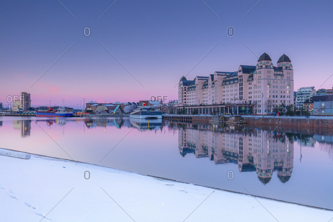 Norway - September 9, 2020: Havnelageret building reflecting in Oslo harbor waters at dawn on a winter morning