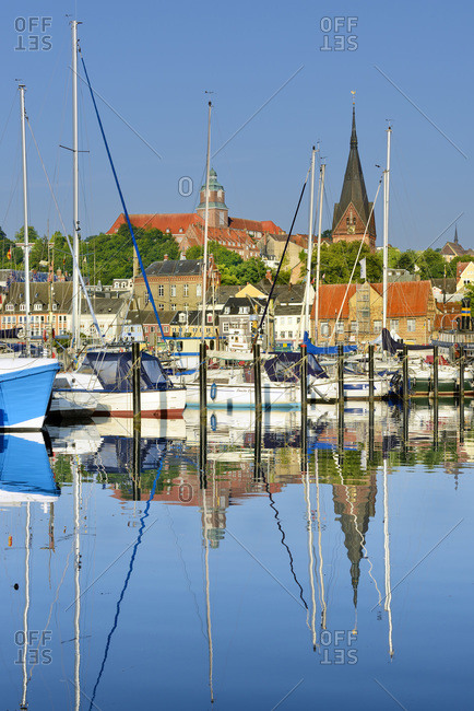 Germany - July 19, 2018: Im Jaich Yachthafen and yachts in the foreground with Flensburg old town and Sankt Marien kirche in the background.