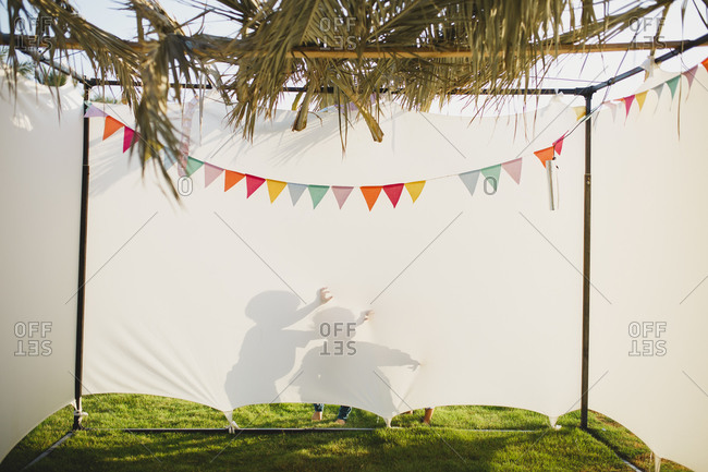 Shadows of children behind a Jewish sukkah