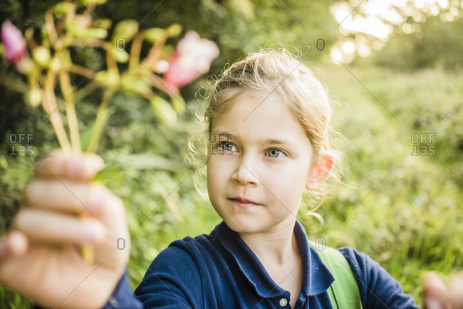 Portrait of girl holding wild flower in the nature