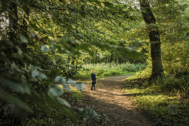 Girl standing on forest path