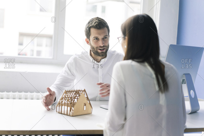 Man explaining architectural model to woman