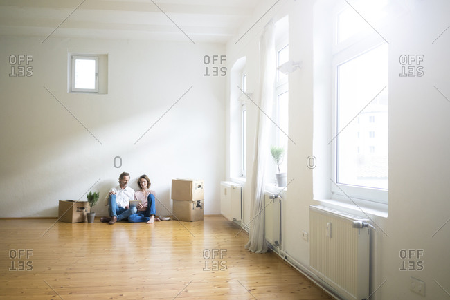 Mature couple sitting on floor in empty room next to cardboard boxes using tablet