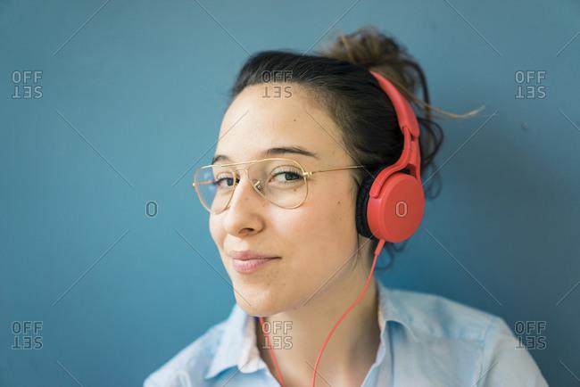 Portrait of smirking woman listening music with headphones