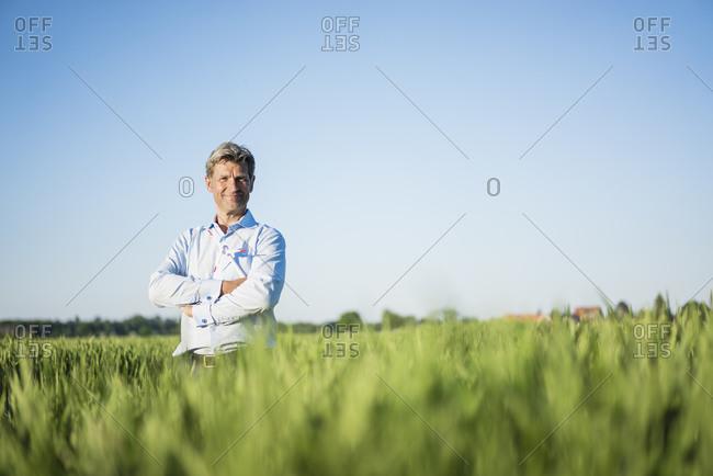Businessman standing in grain field- arms crossed