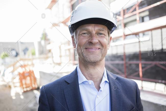 Portrait of confident architect wearing hard hat on construction site
