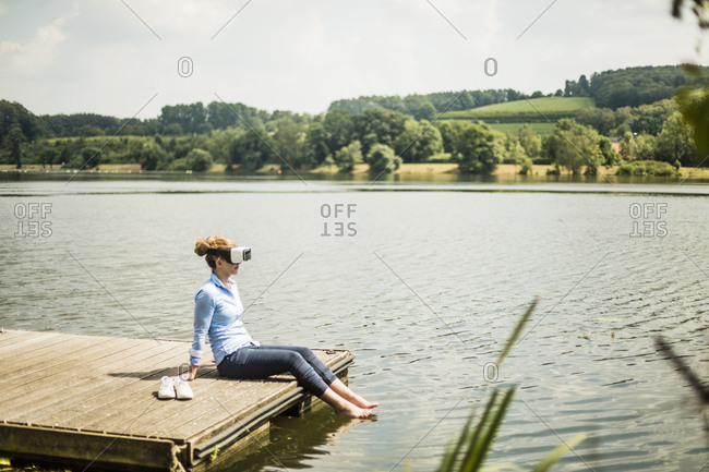 Woman with VR glasses sitting on jetty at a lake with feet in water