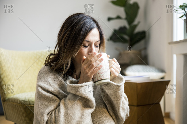 Woman sitting in her comfortable home- drinking tea