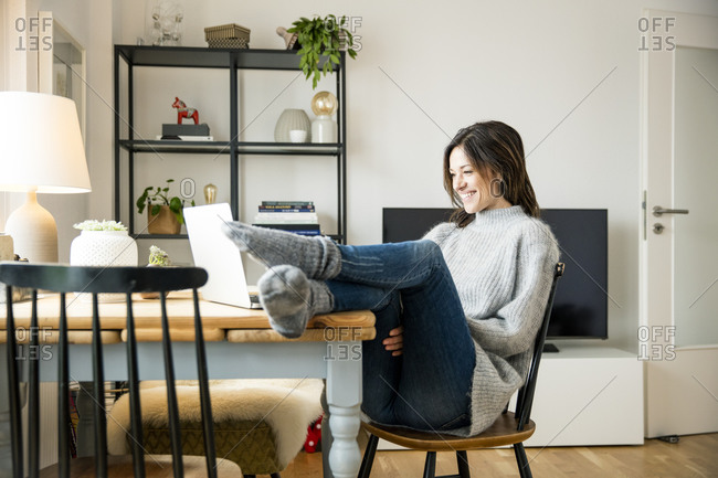 Woman sitting at table with feet up- using laptop