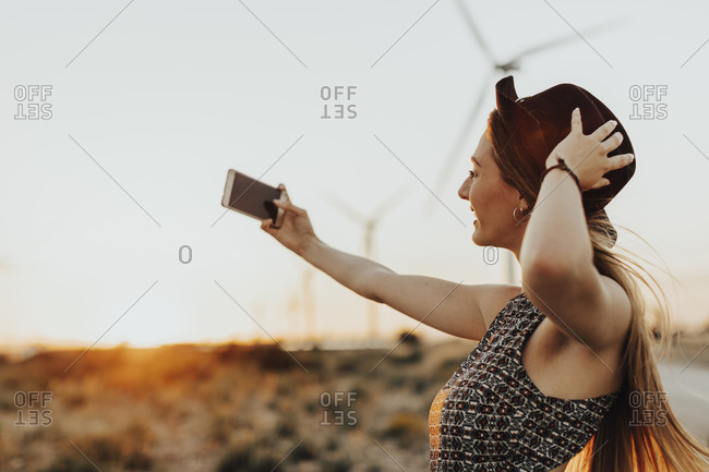 Young woman taking selfie at sunset