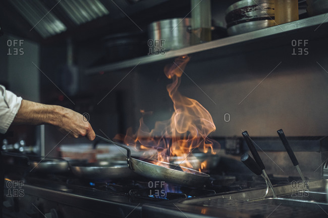 Chef preparing a flambe dish at gas stove in restaurant kitchen
