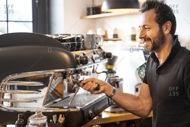 Smiling barista preparing coffee in a coffee shop