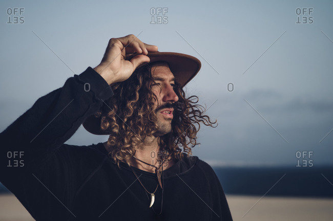 Young man with hat and mustache in the dunes