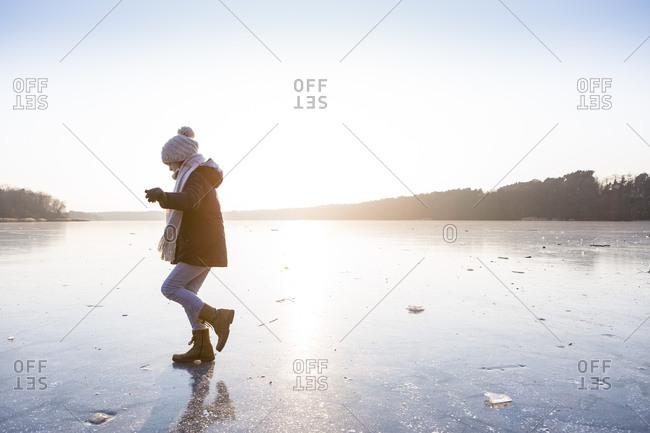 Germany- Brandenburg- Lake Straussee- girl walking on frozen lake