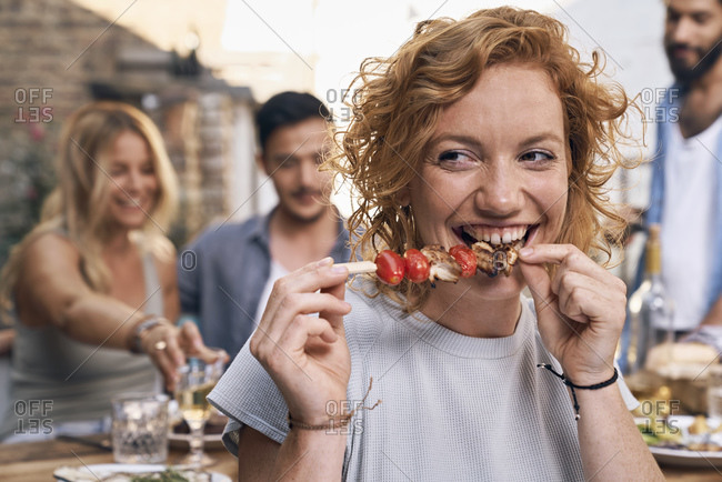 Young woman eating meat skewer at a backyard party with friends