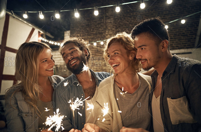 Friends having a backyard party- burning sparklers