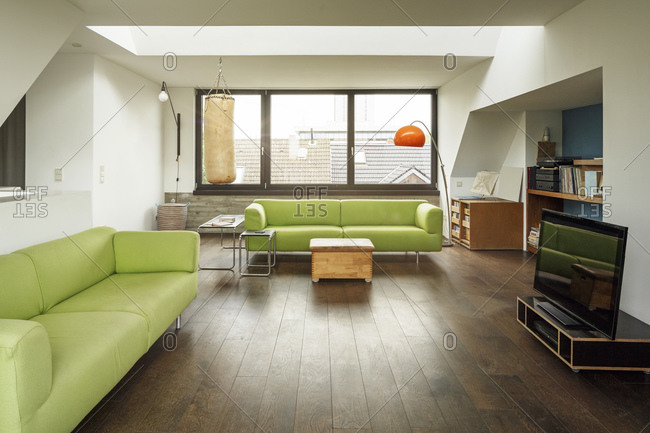 Modern living room with green couches