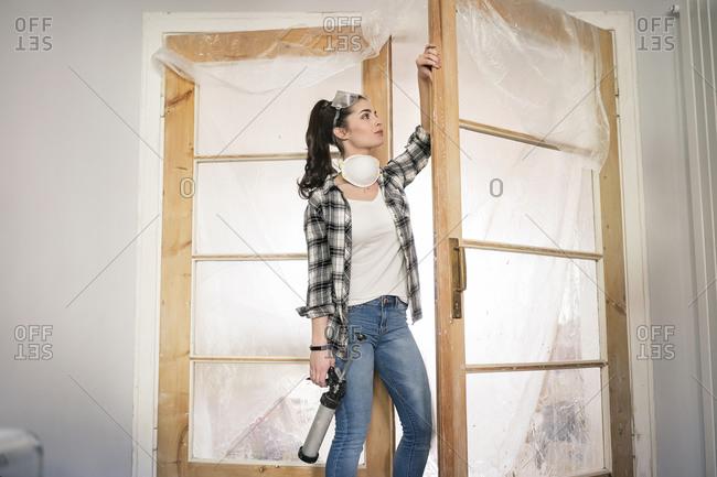 Young woman renovating her new flat- examining door