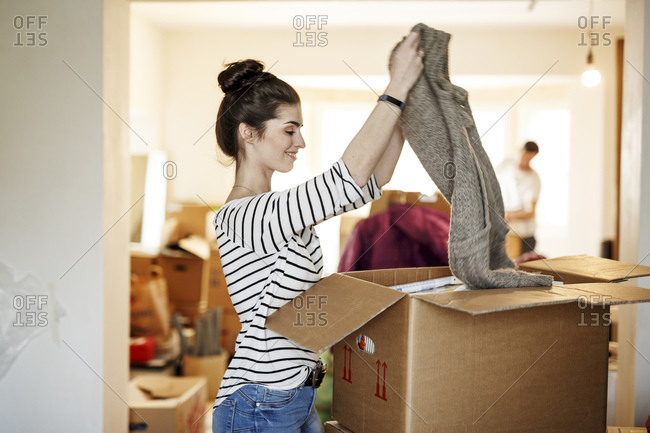 Young woman moving house- unpacking cardboard boxes
