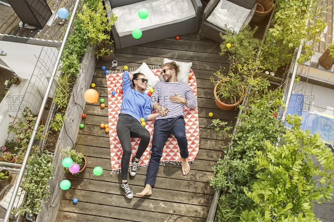 Young couple relaxing on their balcony- lying on blanket with arms around