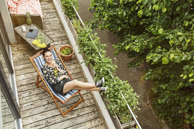 Young woman sitting in deck chair- relaxing on her balcony