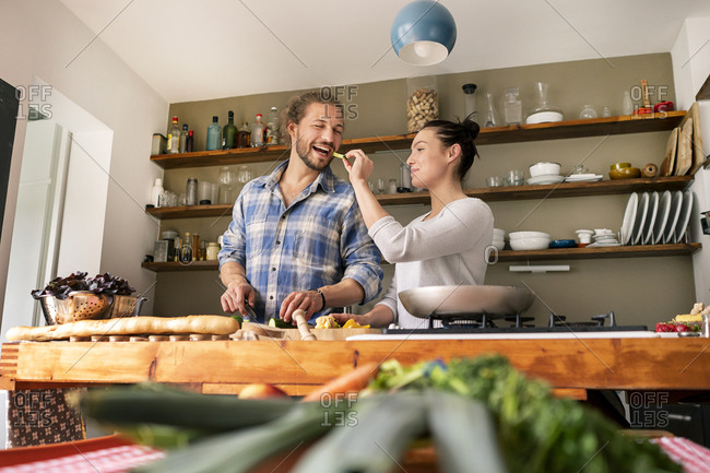 Young couple preparing food together- tasting spaghetti