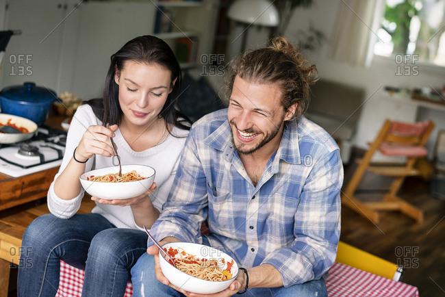 Happy couple sitting on kitchen table- eating spaghetti