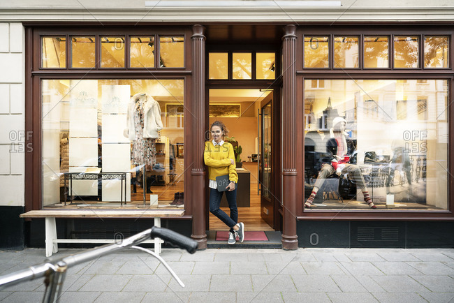 Young woman standing in door of a fashion store- holding laptop