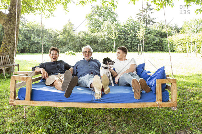 Men of a family sitting on a swing bed in the garden- talking