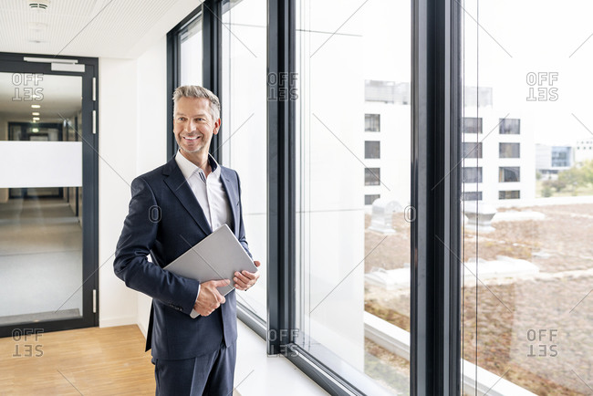 Businessman with laptop in front of window of office building