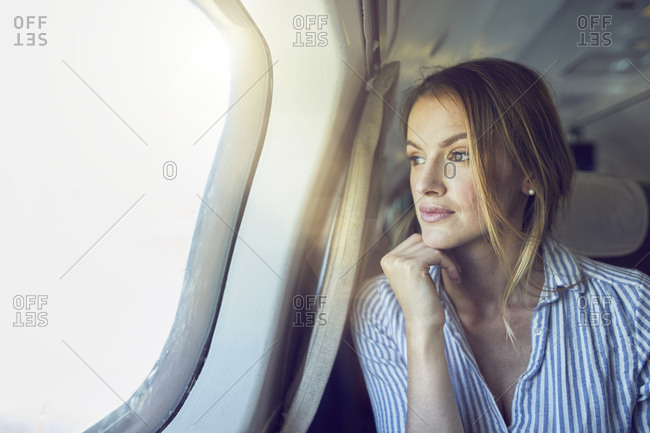 Serious woman looking out of airplane window