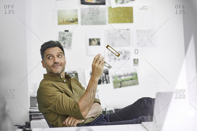 Portrait of smiling man at desk in his office with component