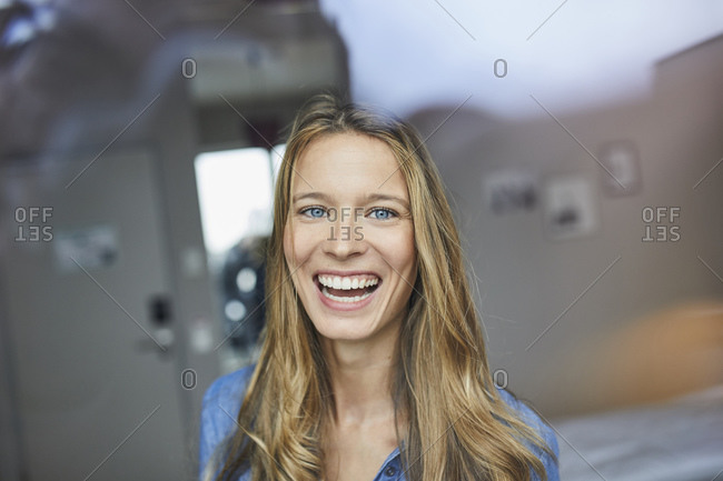Portrait of laughing young woman behind windowpane