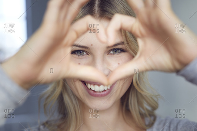 Portrait of laughing woman building heart with her fingers